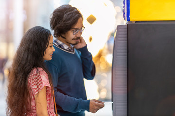Young couple withdrawing money at an ATM