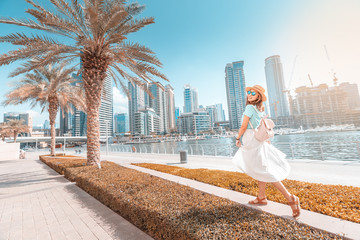 Happy asian girl walking on a promenade in Dubai Marina district. Travel and lifestyle in United Arab Emirates