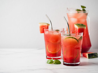 Watermelon cooler with lime, mint and ice. Perfect homemade watermelon drink in glasses with metal straws on white background, copy space left for text