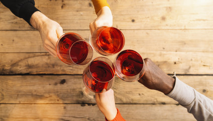 Friends hands toasting red wine glass and having fun cheering with winetasting - Young people...
