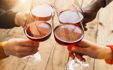 Foto op Aluminium Europa Hands toasting red wine glass and friends having fun cheering at winetasting experience - Young people enjoying time together at wine degustation - Youth and friendship concept