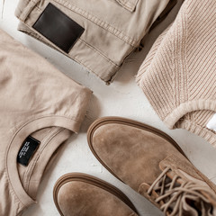 Stylish men's suede boots with fashionable beige casual sweaters with classic trousers on a white table. Trendy spring collection in beige colors for men. Youth modern fashion. Close-up.