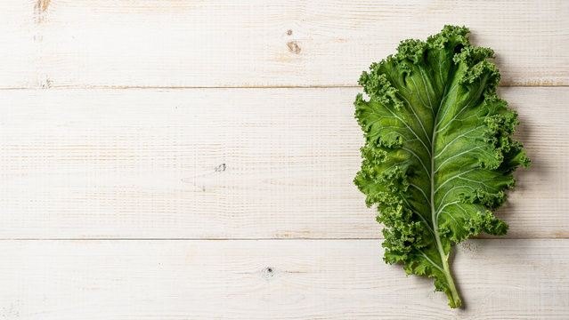 Fresh green kale leaf on white wooden tabletop, copy space left. Flat lay or top view. Healthy detox vegetables. Clean eating and dieting concept. Health kale benefits. Banner