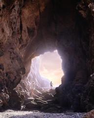 Two boys walking through a cave at sunset, Laguna Beach, California, USA