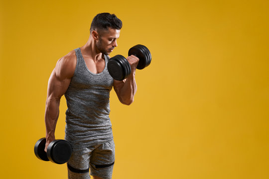 Muscular young man doing exercise with dumbbells