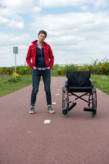 Woman with multiple sclerosis standing outdoors next to her wheelchair, Tilburg-Reeshof, Noord-Brabant, Netherlands