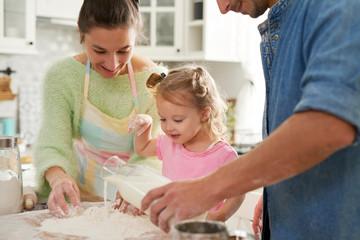 Keuken foto achterwand Koken Baby girl with parents preparing food in the kitchen