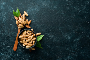 Walnut almonds in the shell. Nuts on a black stone background. Top view. Free space for your text.