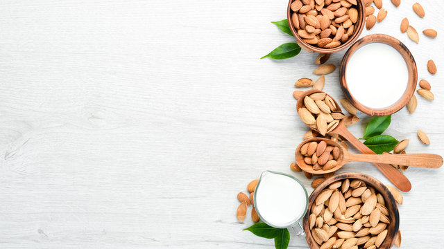 Almond milk and almonds on a white wooden table. Top view. Free space for your text.