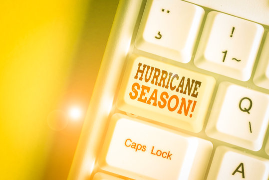 Conceptual hand writing showing Hurricane Season. Concept meaning time when most tropical cyclones are expected to develop White pc keyboard with note paper above the white background