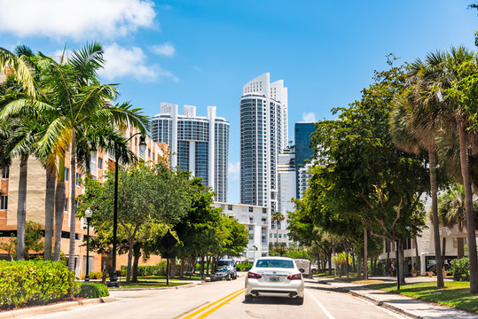 Sunny Isles Beach, USA - May 8, 2018: Modern city in North Miami, Florida, with local road street and car in traffic view of luxury hotel apartment buildings