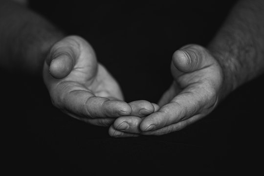 Low key, close up of hands of a faithful mature man praying, hands folded, interlaced fingers in worship to god. Isolated black background. Concept