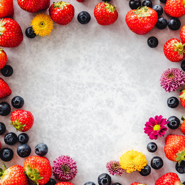 Fresh strawberries, blueberries and chrysanthemum flower border