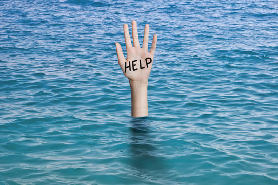 Word help written on the palm of a sinking hand in ocean's water. Drowning person Emergency, failure and help concept. Covid-19 coronavirus epidemic