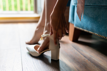 Close-up of slender female legs in classic high-heeled sandals. Women's feet in white high-heeled sandals, one-handed girl adjusts the Shoe, open frame, close-up