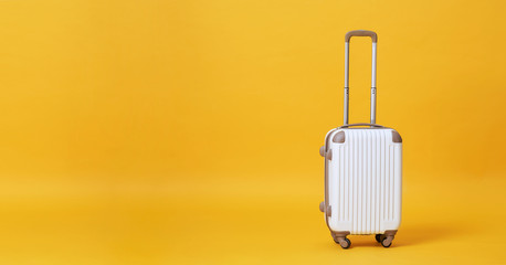 White luggage bag isolated on yellow banner background with copy space for advertisement..