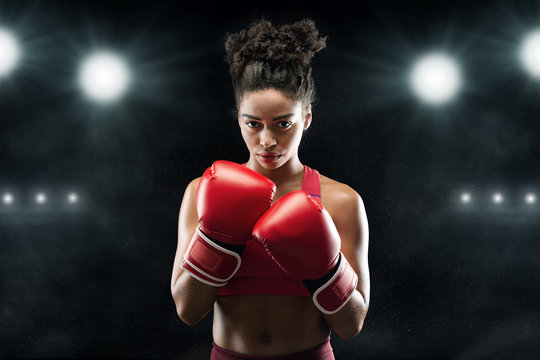 Black woman professional boxer standing in pose, ready to fight