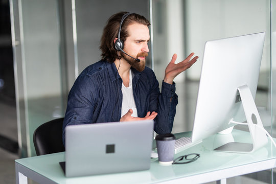 Angry call center operator working at his desk on computer and laptop