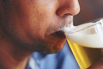 The young man's lips tasting the beer's flavors and feeling the softness of the beer bubbles. Wall mural