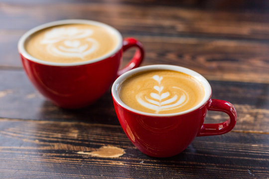 Two red cups of coffee on wooden background with latte art. Table in cafe. Concept of easy breakfast. Small and big ceramic cups