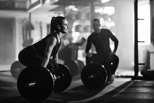 Athletic woman doing deadlift while exercising with barbell in a gym.