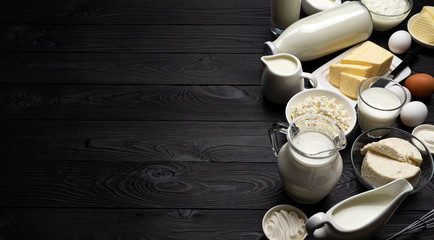 Dairy products on black wooden background, top view