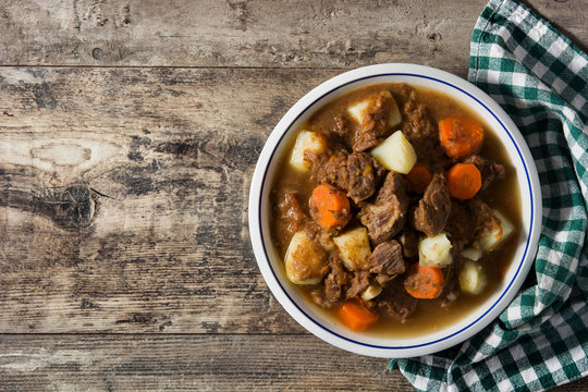 Irish beef stew with carrots and potatoes on wooden table. Top view. Copy space