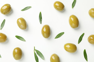 Green olives and leaves on white background, top view