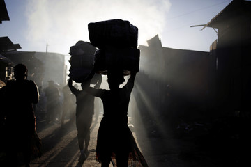 People carry boxes with goods out of a market after a fire, in Port-au-Prince