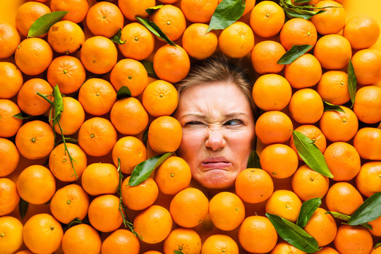Food industry. Face of funny young woman in orange or Mandarin plane.