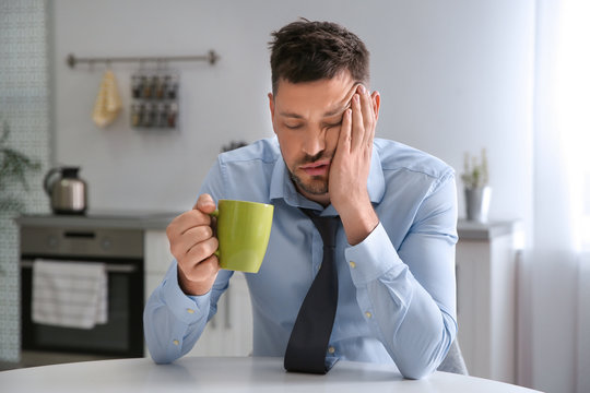 Sleepy man with cup of drink at home in morning