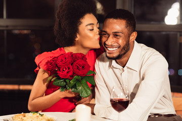 Girlfriend Kissing Boyfriend After Receiving Roses During Date In Restaurant