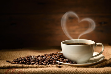 In de dag Cafe Cup of coffee with heart shape smoke and coffee beans on burlap sack on old wooden background