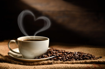 Poster Café en grains Cup of coffee with heart shape smoke and coffee beans on burlap sack on old wooden background