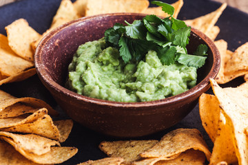 Mexican traditional food, guacamole sauce, ingredients  avocado, cilantro, lime and tortilla corn chips