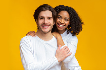 Romantic interracial couple embracing and posing over yellow background