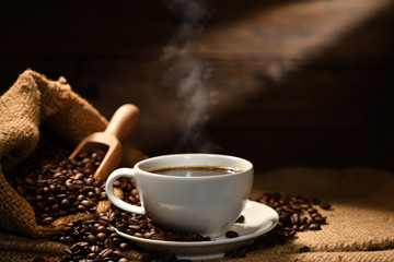 Cup of coffee with smoke and coffee beans on burlap sack on old wooden background