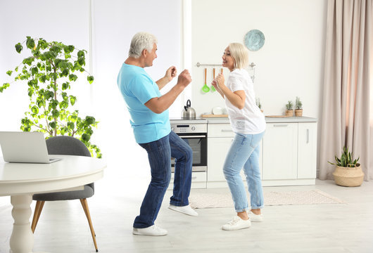 Happy mature couple dancing together in kitchen