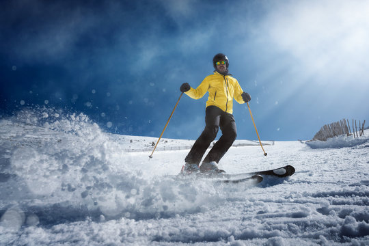 Full body young man in yellow outwear and sunglasses riding skis on snowy mountain slope on sunny winter day on resort