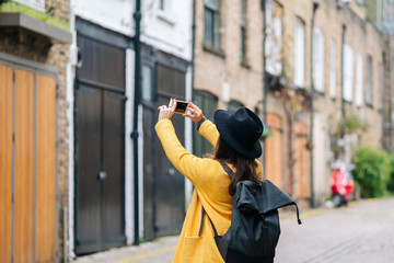 Back view of woman in yellow coat and hat using smartphone to take picture of old building on street of London, United Kingdom