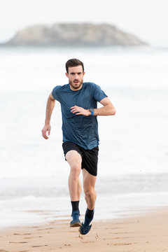 Bearded male athlete in active wear running during empty sandy beach with green mountains on blurred background