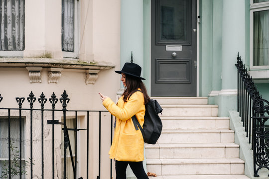 Side view of lady in trendy yellow coat and hat browsing smartphone while walking near shabby house on street of London, United Kingdom