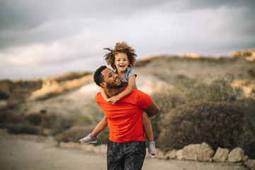 Smiling African American bearded man dressed in sportive clothes carrying cheerful curly active toddler while walking on nature