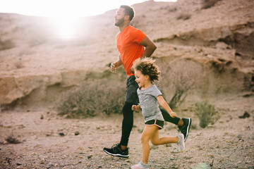 African American bearded active father in red t shirt running with cheerful curly child on desert landscape in backlit
