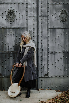 Thoughtful attractive blond female musician gently holding string musical instrument while standing at metal gates