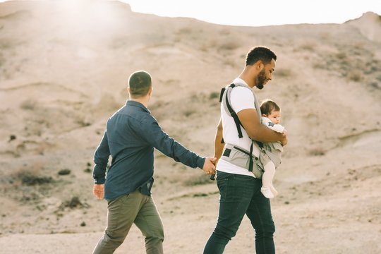 Side view of black casual man holding hand of anonymous male boyfriend and holding little calm baby in grey carrier while strolling on nature at daytime