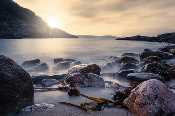 Foggy surface of sea with big rocks on sandy beach and mountains on sunrise at Portonovo beach at Italy