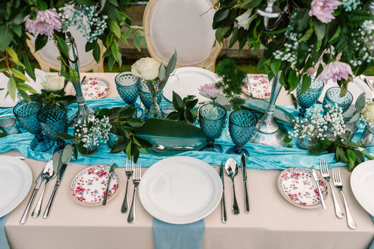 From above of wedding table decorated with blue and beige cloth and flowers bouquets in tall vases and served with porcelain plates and blue glasses