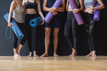Group of young sporty man and women with yoga mats standing at black wall smiling and talking after practicing yoga, Yoga and fitness work out healthcare lifestyle in fitness club
