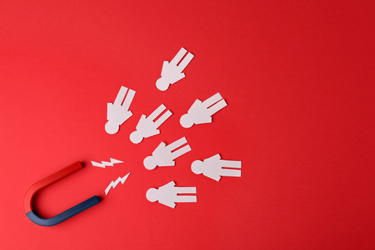Magnet and paper people on red background, flat lay